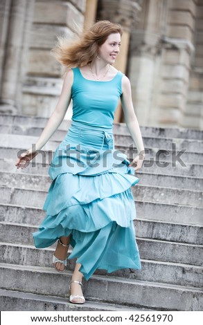 Young woman in dress running down on stairs. - stock photo