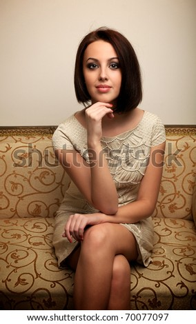 Young woman in dress sitting on the couch - stock photo
