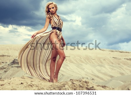 Young woman in dress standing on sand