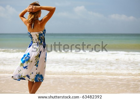 Young woman in dress standing on sand and looking to a sea
