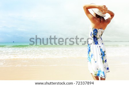 Young woman in dress standing on sand near sea and holding a hat - stock photo