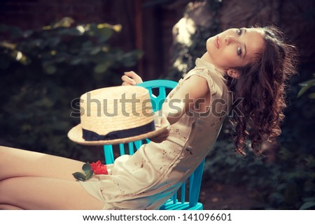 young woman in elegant dress sit on chair in garden with hat in hand summer day - stock photo