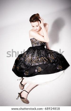 young woman in elegant dress sit pensive on the floor, studio shot - stock photo