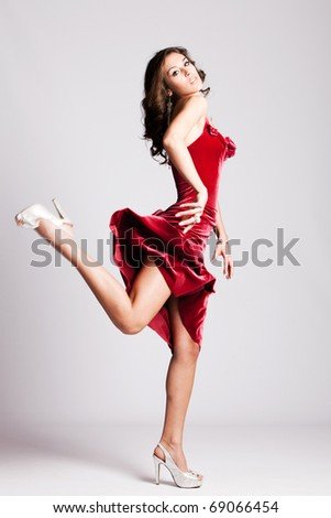 young woman in elegant red dress run, studio shot - stock photo