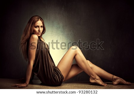 young woman in elegant short dress sit  barefoot, full body shot, studio shot - stock photo