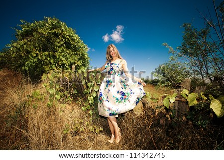 young woman in elegant silky dress at countryside autumn sunny day - stock photo