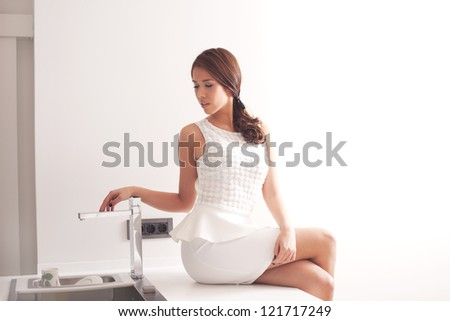 young woman in elegant white dress in modern kitchen