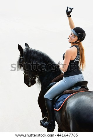 "Young woman in equestrian outfit riding a horse. Girl shows gesture "" victory """