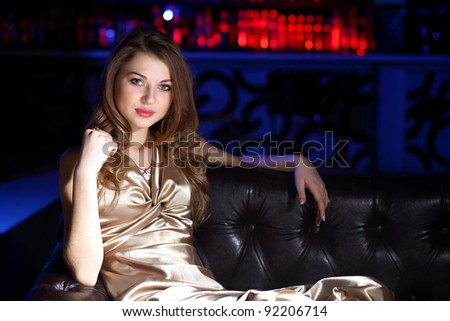 Young woman in evening dress in night club with a drink