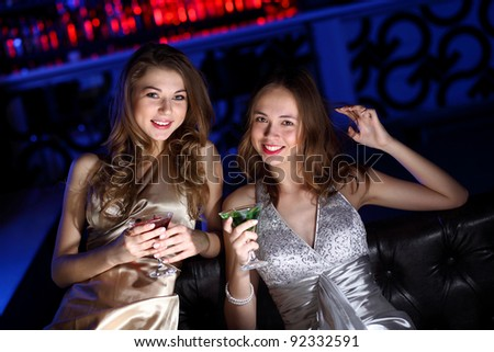Young woman in evening dress in night club with a drink - stock photo