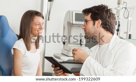 Young Woman In Exam Room With Ophthalmologist Using Digital Tablet - stock photo