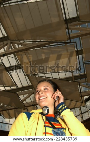 Young woman in factory building using mobile phone - stock photo