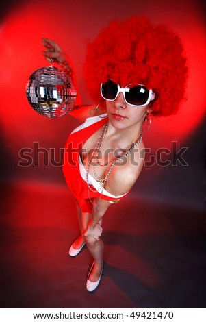 young woman in fancy dress holding a disco ball - stock photo