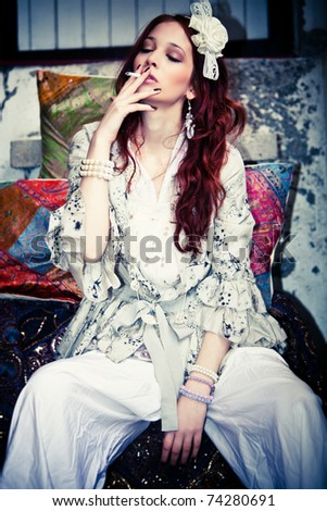 young woman in fashionable clothes smoking, outdoor shot - stock photo