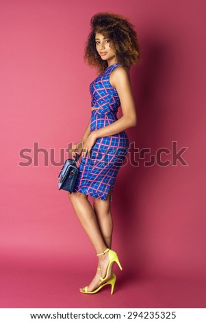 Young woman in fashionable dress holding purse on pink background. Afro hairstyle