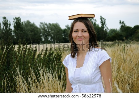 Young woman in field with book on the head - stock photo