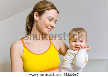 Young woman in fitness clothes with her baby girl - stock photo