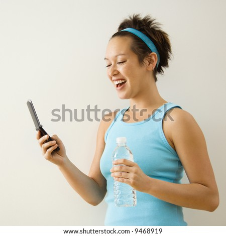 Young woman in fitness clothing holding bottled water and smiling at cellphone. - stock photo