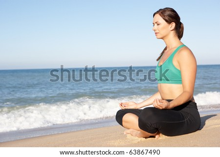 Young Woman In Fitness Clothing Meditating On Beach