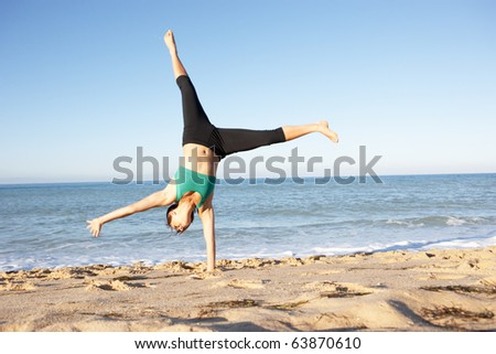 Young Woman In Fitness Clothing Turning Cartwheel On Beach - stock photo