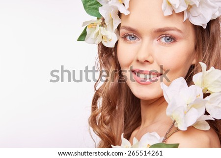 Young woman in floral wreath looking at camera