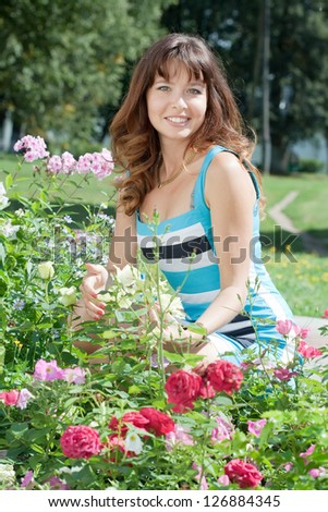 young woman in flowers plant at garden - stock photo