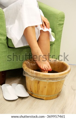Young woman in foot-bath in oriental herb water for body detox - stock photo