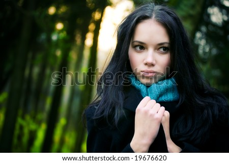 Young woman in forest. Mysterious portrait. - stock photo