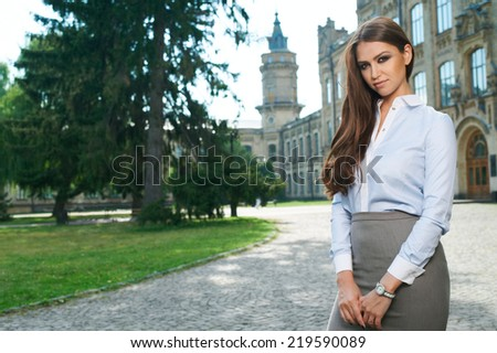 young woman in formal clothes near old university building