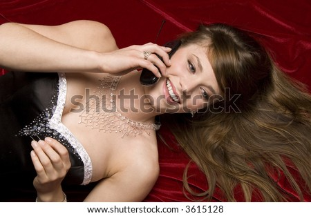 Young woman in formal dress lying down talking on phone - stock photo