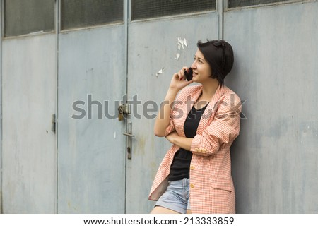 Young woman in front of a garage talking on the phone - stock photo