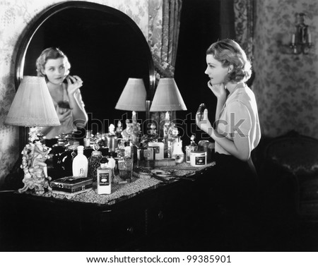 Young woman in front of her vanity applying make-up - stock photo