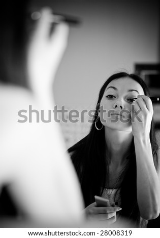 Young woman in front of mirror in make-up room. Black and white concept. - stock photo