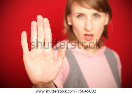 young woman in front of red background saying no shielding with flat hand (focus on hand)