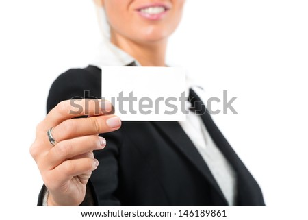 Young woman in front of white background, she introduces themselves with a businesscard, maybe she is a businesswoman or laywer - stock photo