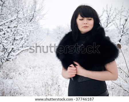 young woman in fur coat outdoors in snow garden - stock photo