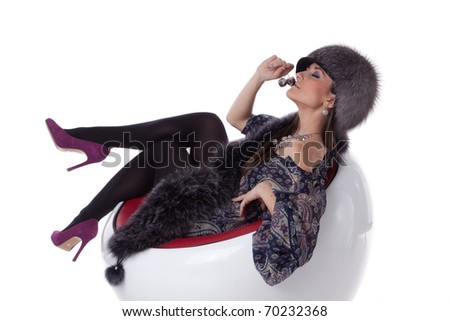Young woman in fur with cherry sit on armchair on a white background.