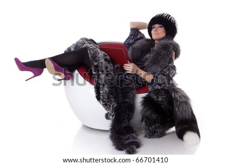 Young woman in fur with laptop sit on armchair on a white background.