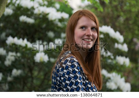 Young woman in garden against a backdrop of Rhododendron. - stock photo