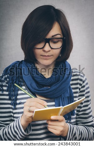 young woman in glasses writes something in a notebook - stock photo