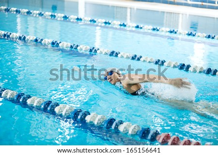 Young woman in goggles and cap swimming front crawl stroke style in the blue water indoor race pool - stock photo