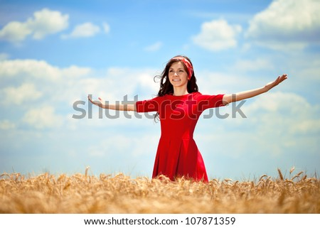 Young woman in golden wheat- freedom concept