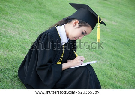 Young woman in graduation gowns write notebook