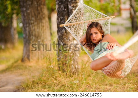 Young woman in green dress rest in hammock