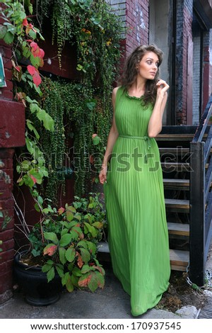 Young woman in green long dress walking outsige her home - stock photo