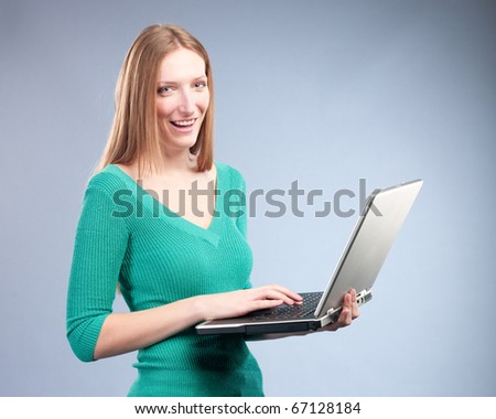 Young woman in green sweater standing and holding laptop computer - stock photo