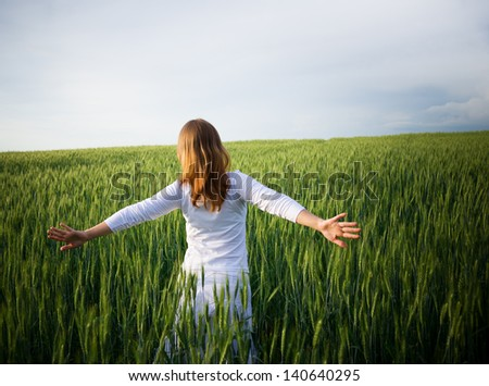 young woman in green wheat field