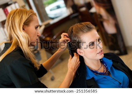 Young woman in hairdresser saloon having a haircut - stock photo