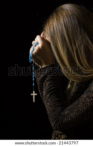 Young woman in half face praying with rosary in dark - stock photo
