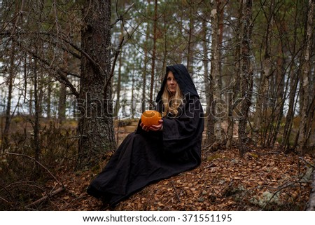 Young woman in Halloween witch costume in the autumn forest with yellow pumpkin.